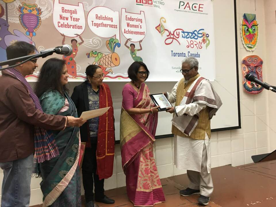 Poet Asad Chowdhury hands over PACE-RMM Women Achievers Award 2018 to Dr. Tanjina Mirza, Chief Programs Officer, Plan International Canada.